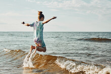 Girl Enjoying Sea Jumping Over Waves Spending A Free Time Over Sea On A Beach At Sunset During Summer Vacation