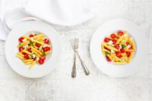 Two Plates Of Vegetarian Pasta WithÔøΩmozzarella, Cherry Tomatoes And Basil