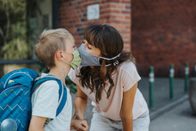Mother Kissing Son Wearing Protective Face Mask Standing In Font Of School