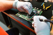 Technician soldering circuit board of electrical component at workbench in electronics repair shop