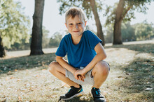 Smiling Boy Crouching In Pubic Park On Sunny Day