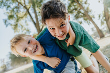 Smiling Brothers With Arm Around Kneeling In Public Park On Sunny Day