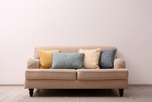 Comfortable Beige Sofa Near Light Wall Indoors, Space For Text. Simple Interior
