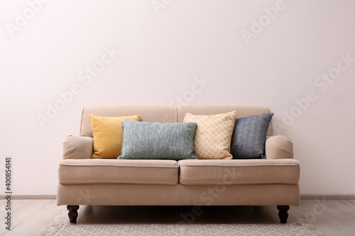 Fototapeta Comfortable beige sofa near light wall indoors, space for text. Simple interior obraz
