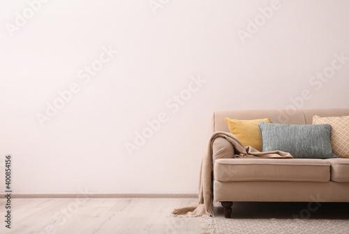 Fototapeta Comfortable beige sofa near light wall indoors, space for text. Simple interior obraz