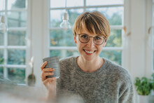 Smiling Mid Adult Woman Holding Tea Cup While Standing At Home
