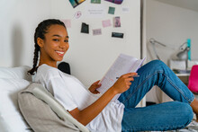 Teenage Girl Writing In Exercise Book While Sitting On Bed At Home
