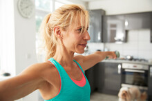 Mature Woman With Arms Outstretched Exercising At Home
