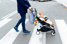 Man With Baby Stroller Crossing Road In City