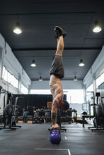 Male Athlete Balancing Upside Down On Kettlebells In Gym