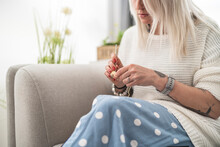 Mid Adult Woman Crocheting Pacifier While Sitting On Sofa At Home