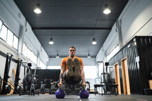Male Athlete Exercising With Kettle Bell In Gym