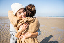 Daughter And Mother Embracing Each Other While Standing At Beach