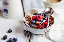 Bowl Of Homemade Cereals With Coconut, Raspberries And Blueberries