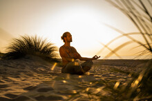 Shirtless Man Meditating While Practicing Yoga On Sand At Beach Against Clear Sky During Sunset