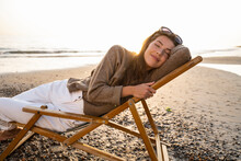 Smiling Beautiful Young Woman Reclining On Folding Chair While Relaxing At Beach During Sunset