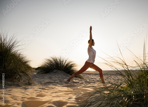 Young woman practicing warrior position yoga amidst plants at beach against clear sky during sunset