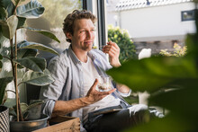 Mid Adult Man Smiling While Eating Food Sitting At Home