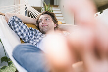 Mid Adult Man Resting In Hammock With Hands Behind Head At Home