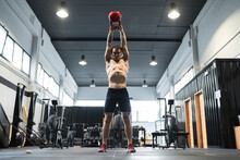 Male Athlete Lifting Kettlebell While Standing In Exercise Room