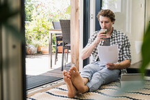 Mid Adult Man Drinking Juice Holding Paper While Sitting At Home
