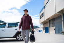 Mid Adult Man Walking With Gym Bag At Parking Lot On Sunny Day