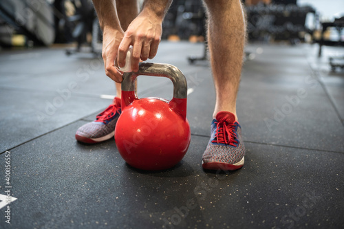 Legs of man holding kettlebell while standing in gym