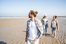 Man Looking Away While Walking With Women Talking In Background At Beach