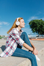 Woman Listening Music Through Headphone Looking Away While Sitting On Footpath During Sunny Day