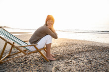 Smiling Young Woman Sitting On Folding Chair While Looking Away At Beach Against Clear Sky During Sunset
