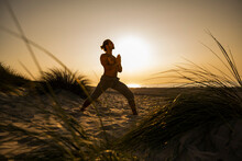 Shirtless Young Man Practicing Warrior Position Yoga With Hands Clasped At Beach Against Clear Sky During Sunset