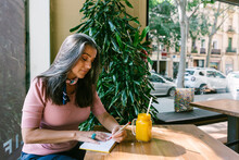 Mature Woman Writing In Diary While Sitting With Fresh Juice At Table In Cafe