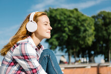 Woman With Eyes Closed Listening Music Through Headphone On Sunny Day