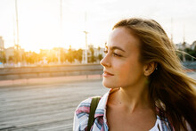 Attractive Woman Looking Away While Standing On Street During Sunny Day