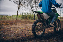 Teenage Boy Riding Motorcycle On Dirt Road In Forest