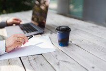 Male Entrepreneur With Disposable Coffee Cup Working At Wooden Table