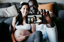 Smiling Young Man With Pregnant Woman Taking Selfie At Home