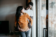 Happy Young Man Looking At Pregnant Woman While Standing By Window At Home