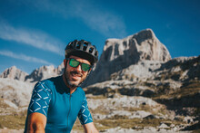 Smiling Mid Adult Male Cyclist Wearing Cycling Helmet And Sunglasses At Picos De Europa National Park, Cantabria, Spain