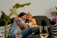 Mother And Daughter Laughing While Embracing Each Other On Sofa In Living Room
