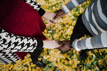 Multi Ethnic Couple Holding Hands While Standing In Park During Autumn