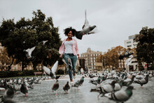 Cheerful Woman Running Amidst Flock On Pigeons At Park In City