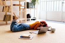 Redhead Woman With Book And Laptop Lying On Carpet At Home