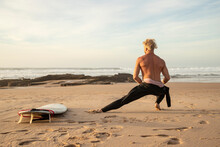 Shirtless Male Surfer Stretching By Surfboard At Beach
