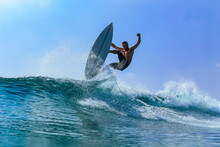 Man With Surfboard Surfing On Sea Wave Against Clear Sky
