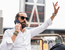 Portrait Of Bearded Businessman Wearing Sunglasses Waving While Talking On Smart Phone