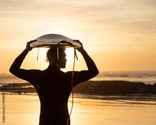 Silhouette surfer carrying surfboard over head at beach during sunset
