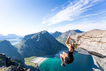 Mid Adult Woman Hanging On Edge Of Mountain At Ryten, Lofoten, Norway