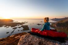 Hiker Admiring View While Sitting In Sleeping Bag On Mountain At Volandstinden, Lofoten, Norway