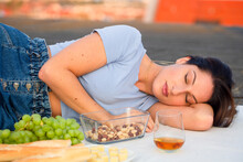 Young Woman Sleeping At Picnic On Rooftop